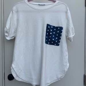 White top with blue pattern pocket